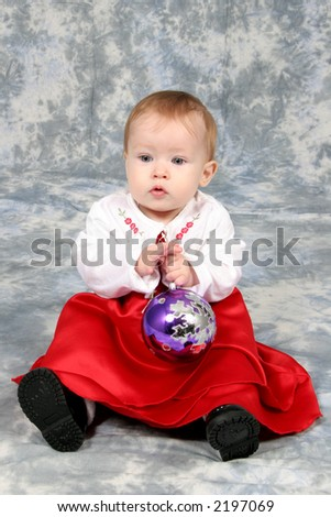 Little Baby Girl in Christmas dress with blub in hand - stock photo
