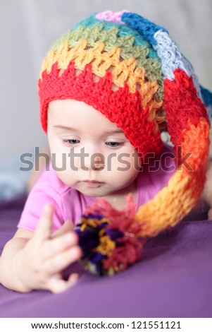 Little baby girl in colorful reggae knit hat - stock photo