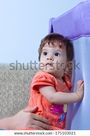 Little baby girl in orange dress standing  on feet