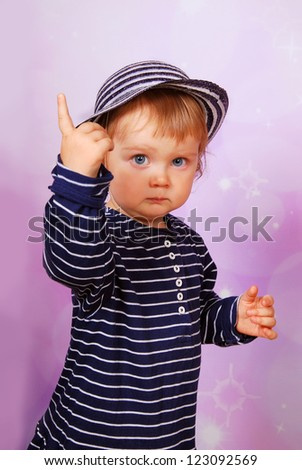 little baby girl in striped dress and hat pointing of the finger - stock photo