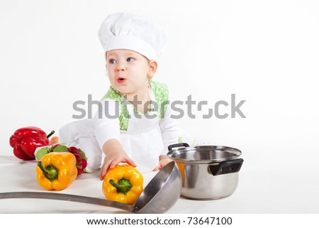 Little baby girl in the cook costume sitting near pan and vegetables. - stock photo