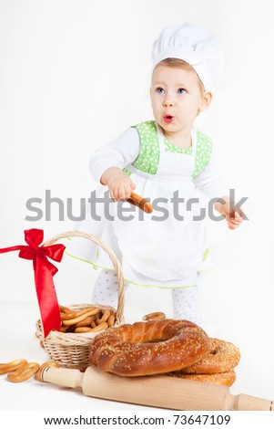 Little baby girl in the cook costume standing near bread rolls and bagels. She is looks surprised.