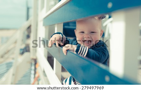 little baby girl laughing and having fun on a beachhouse - stock photo