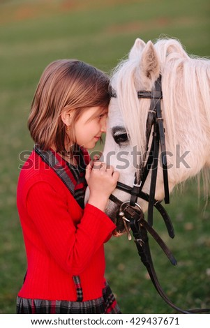 Little baby girl Little white horse looking at each other Outdoors - stock photo