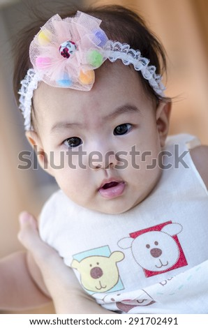 Little baby girl looking into camera - stock photo