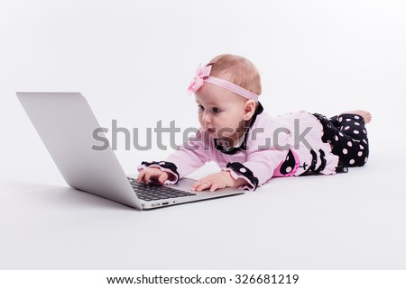 little baby girl lying on her stomach in a smart pink and black dress and a bandage on his head on a white background in front of a laptop and learns to type on it, photograph with depth of field