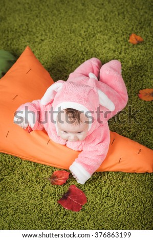 Little baby girl lying on the green carpet in a bunny suit - stock photo