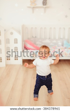 Little baby girl makes her first steps in kids room - stock photo