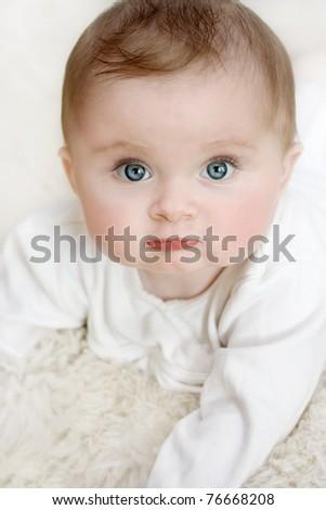 Little baby girl on a white blanket - stock photo