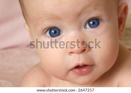 Little Baby Girl on belly with big blue eyes taken closeup