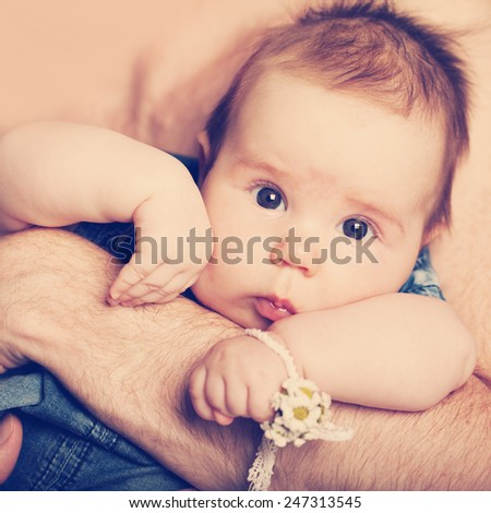 Little baby girl on father's hands - stock photo