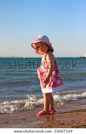 Little baby girl on the beach - stock photo