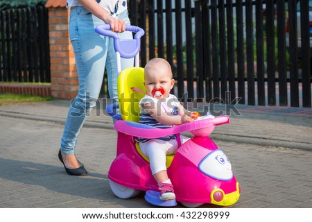 Little baby girl on the ride on car - stock photo