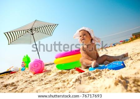 Little baby girl on the sand beach with beach toys - stock photo