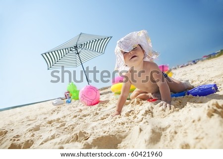 Little baby girl on the sand beach with hat and beach toys - stock photo