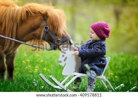 Little baby girl on wooden rocking horse and pony