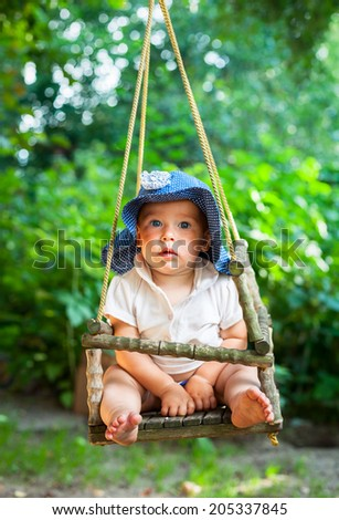 Little baby girl  playing in a summer garden - stock photo