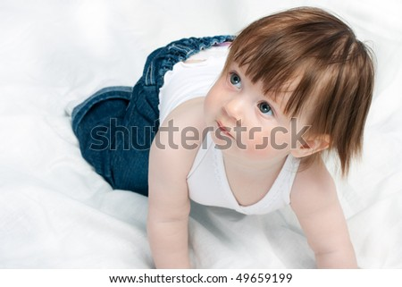 little baby girl playing on the bed