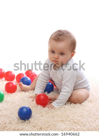 Little baby girl playing with balls - stock photo