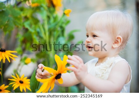 little baby girl playing with flowers and tears flowers in the park or garden - stock photo