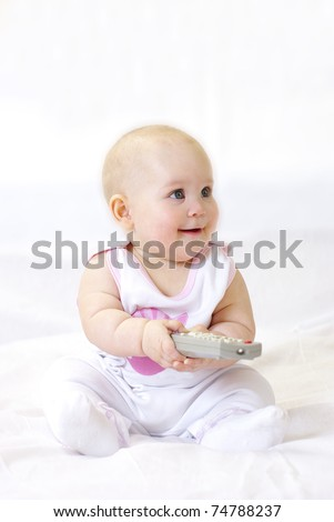 Little baby girl playing with TV remote - stock photo