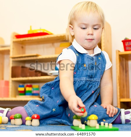 Little baby girl playing with wooden toys at nursery - stock photo