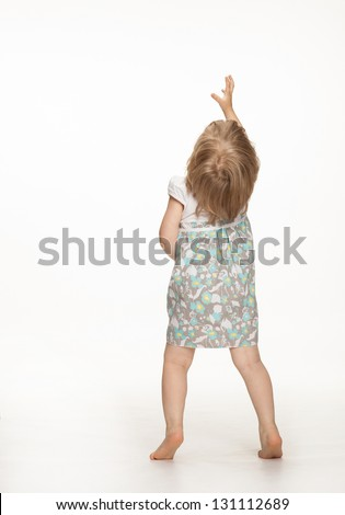 Little baby girl showing something above her, rear view; white background - stock photo