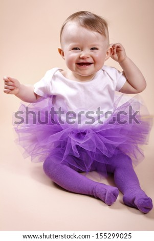 Little baby girl sitting in tutu skirt - stock photo