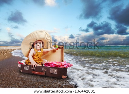 Little baby girl  sitting into retro suitcase at the sea coast - stock photo