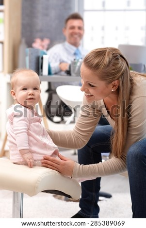 Little baby girl sitting on a chair, mother holding her, sitting opposite, smiling.