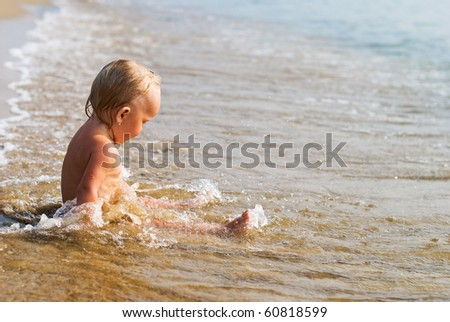 Little baby girl sitting on the beach and playing in waves. - stock photo