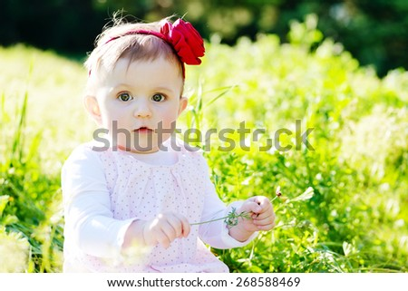 little baby girl sitting on the meadow - stock photo
