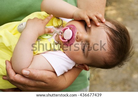 Little baby girl sleeping outdoor. Close up of grandmother hand holding little baby.  - stock photo