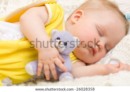 Little baby girl sleeping with her bear toy - stock photo