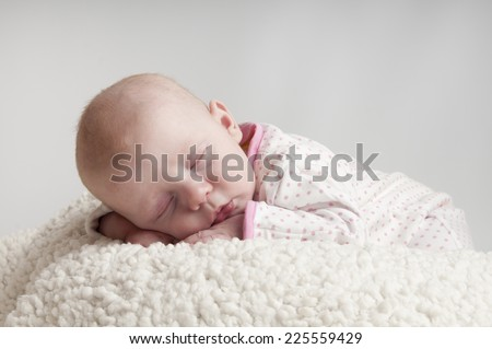 little baby girl sleeps on a fur bad - stock photo