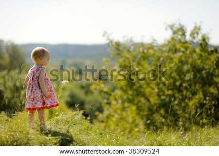 Little baby girl standing on the edge of a cliff