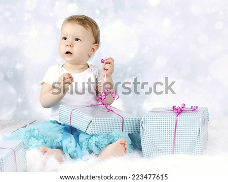 Little baby girl unwrapping christmas presents - stock photo