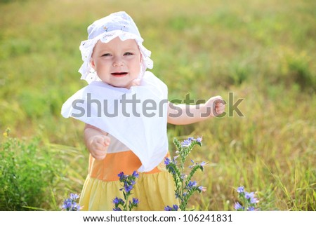 Little baby girl walking by green field on sunny day