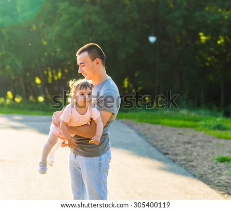 Little baby girl walking in a summer park with her father - stock photo