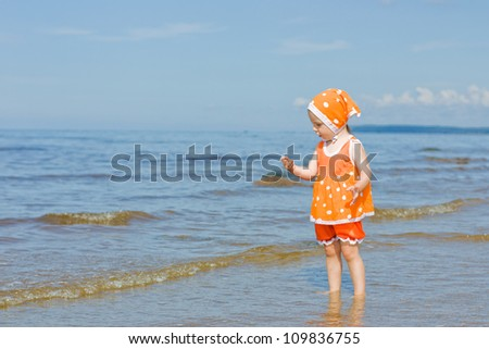 Little baby girl walking on the beach