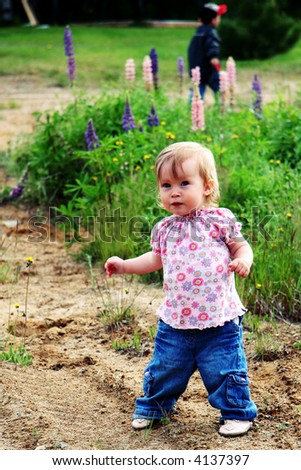 Little Baby girl walking outside with boy in background