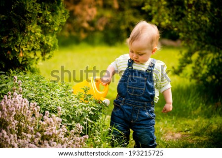 Little baby girl waters plants in backyard garden with watering can