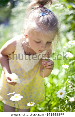 little baby girl with daisy in her hand - stock photo