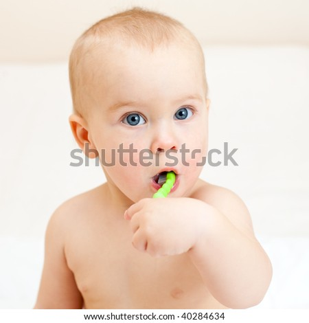 Little baby girl with green tooth brush - stock photo