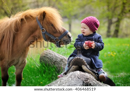 Little baby girl  with red apple and pony - stock photo