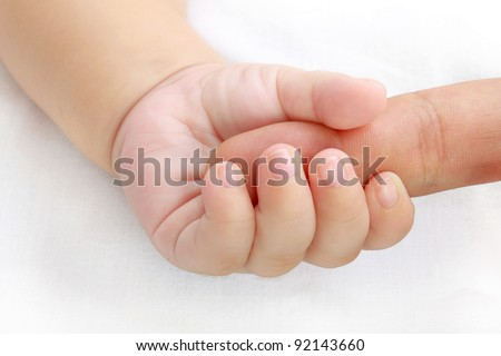 little baby hand holding a mother's finger - stock photo