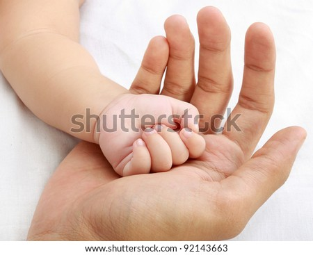 little baby hand with father's hand - stock photo