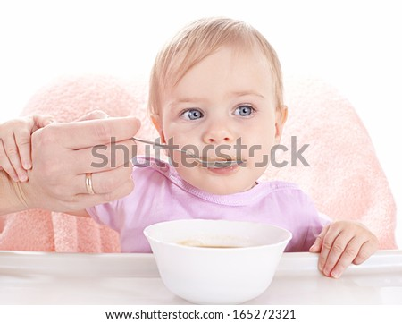 Little baby having fun eating children's porridge - stock photo
