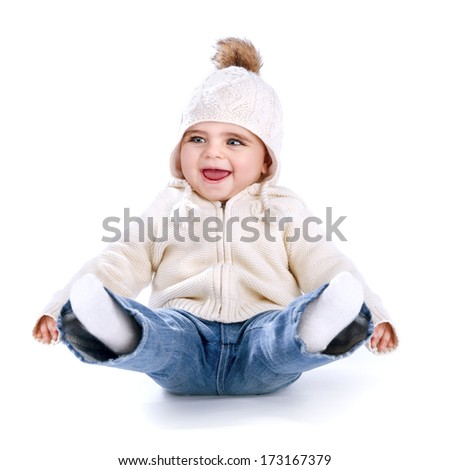 Little baby having fun in the studio isolated on white background, sitting on the floor with legs up, wearing warm stylish hat, winter activity concept - stock photo