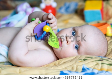 Little baby holding a rattle and lies on a blanket with toys - stock photo